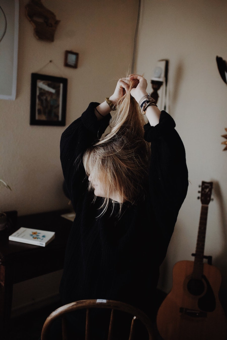 A woman tying back her hair with her guitar next to her.